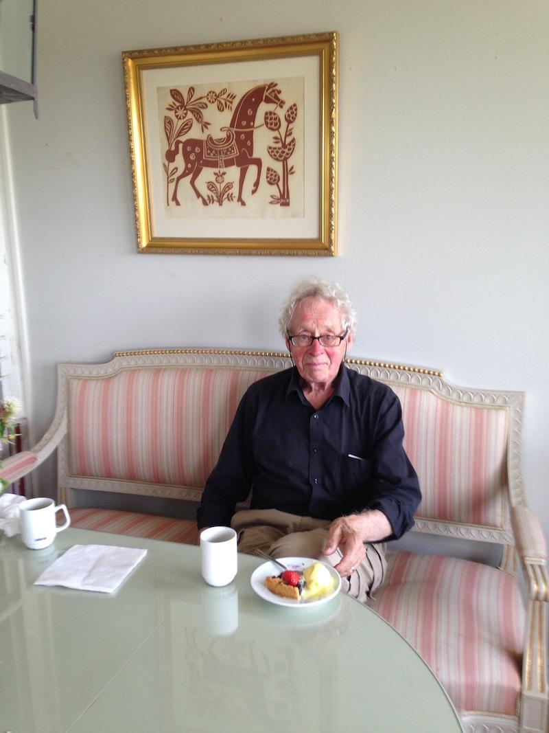 fotografi på Jerk-Olof Werkmäster som sitter i en soffa och har en tavla av sin far Jerk Werkmäster bakom sig